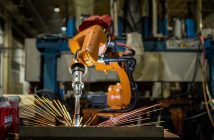 Robot is welding metal part in automotive industrial