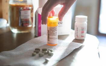 Kristen Kilmer spreads out her daily medications, including Lynparza (center), which costs nearly $17,000 per month. (Kristina Barker for KHN)